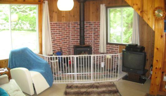 Salon avec poêle au bois protégé par une barrière amovible.